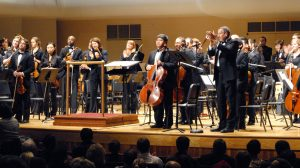 Huxford Symphony Orchestra stands on stage for applause