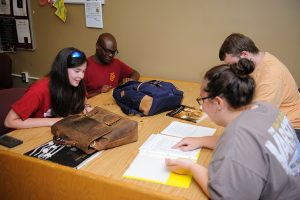 four students studying together around a table