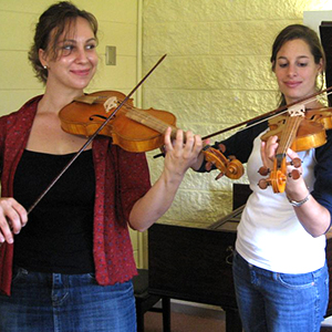 two students practicing violin